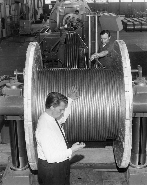 Employees monitor the winding of a large aluminum cable onto a large wooden spool.