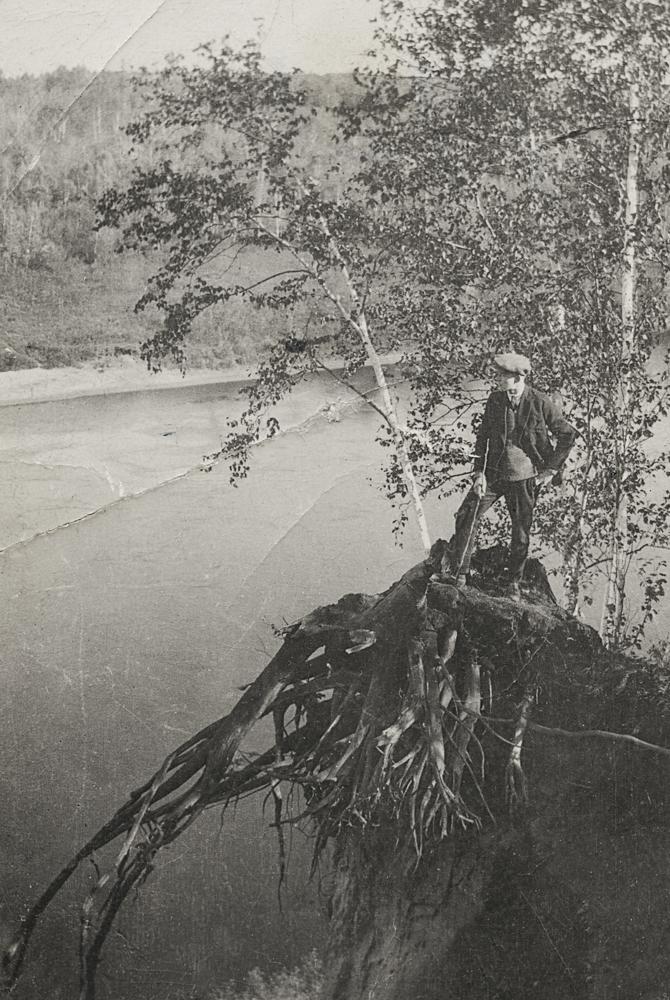 Frank Sutcliffe se tient debout sur une souche surplombant la rivière.