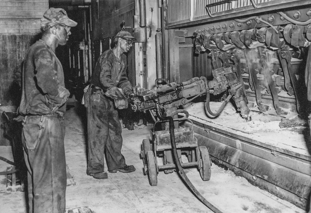 Two employees, wearing wool clothing, caps and small glasses, are handling machinery near an aluminum pot.