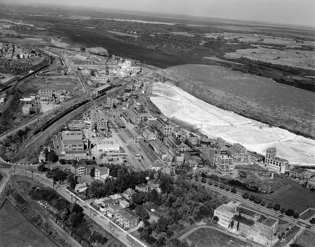 Aerial view of the vast mill site that stretches near the river on which floats both thousands of logs and a whitish lime residue.