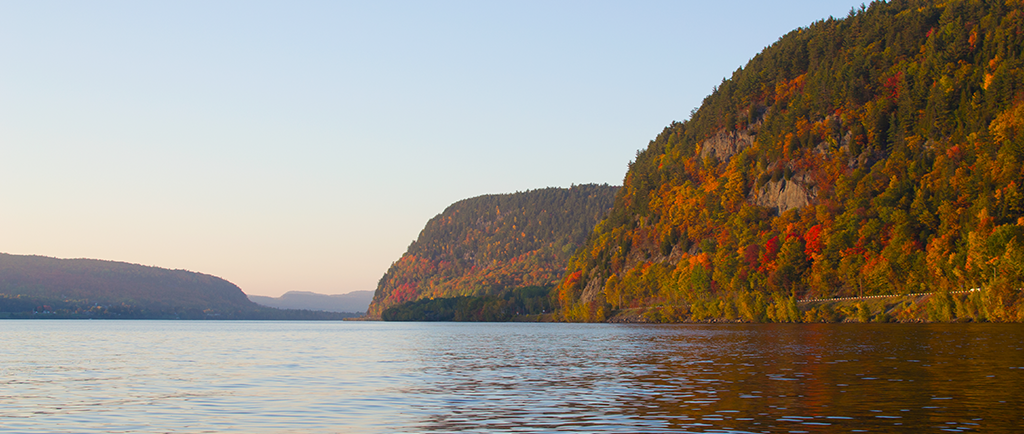 The Saint-Maurice River flows between high cliffs covered with autumn-coloured trees