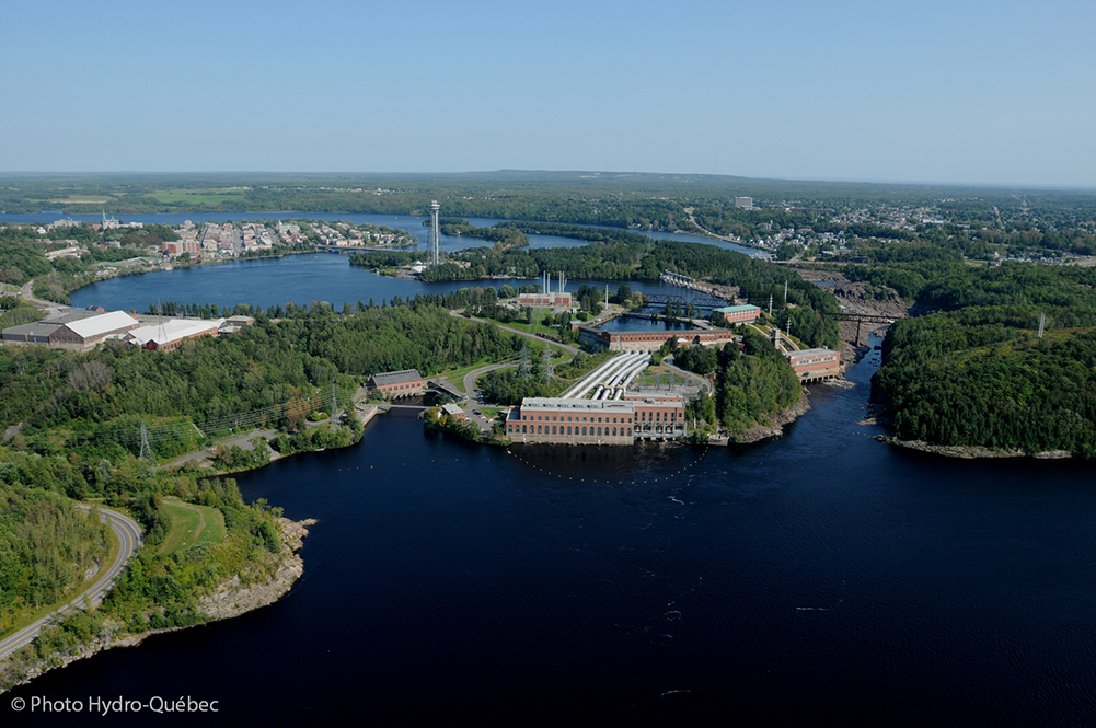 Aerial view of Shawinigan that shows the bay, the falls and three hydro-electric power plants. In the distance is the city centre and the Cité de l'énergie tower that stands on an island in the middle of the river.