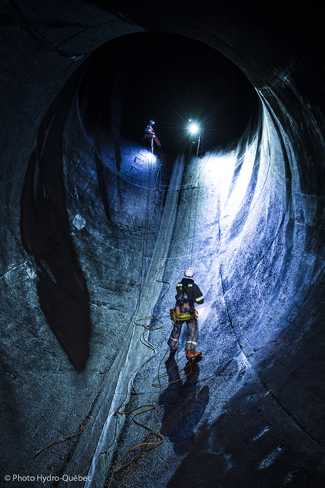 A worker with climbing equipment stands in the light of a searchlight inside a huge concrete tunnel, which functions as a penstock.