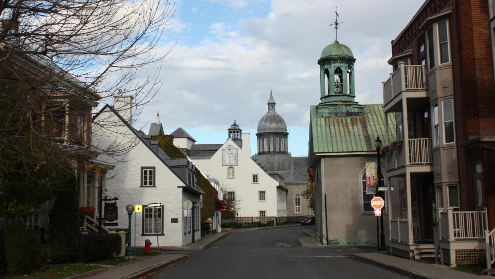 De vieux bâtiments encadrent la rue étroite. Deux clochers sont visibles, presque l'un en face de l'autre.