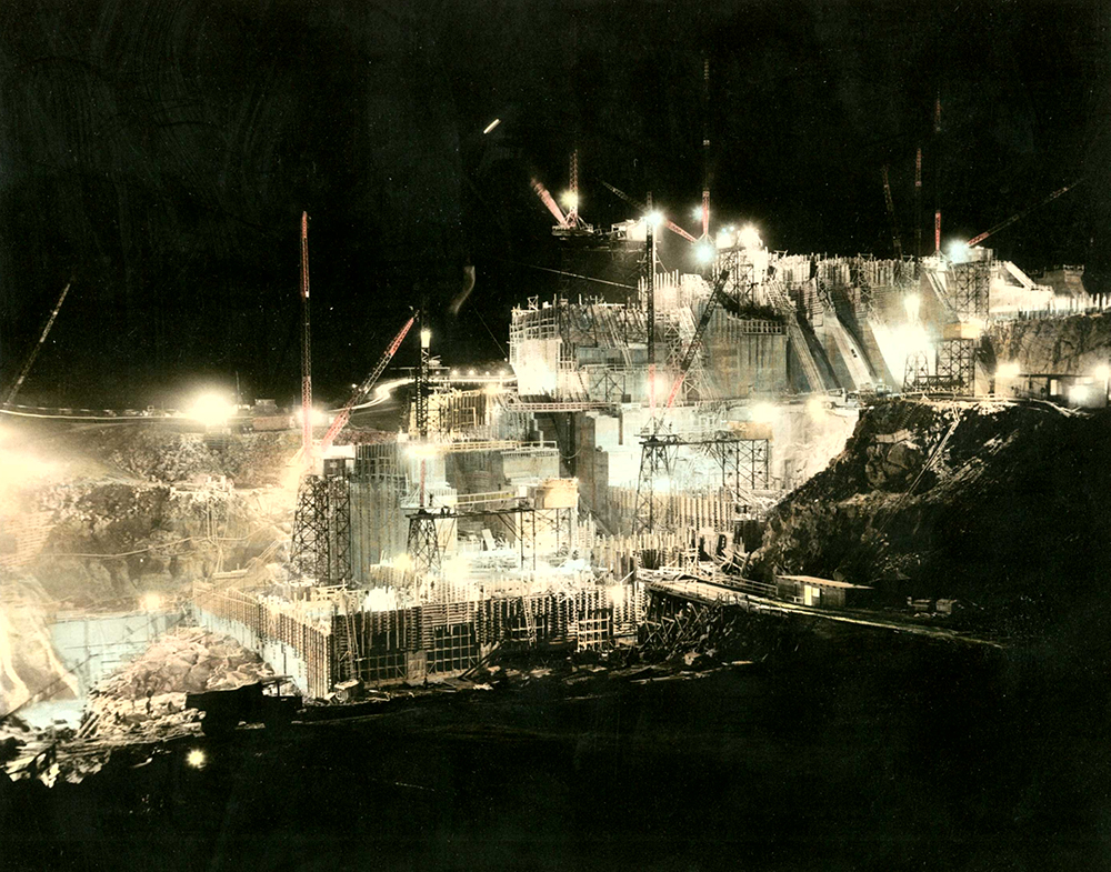 Site of a dam under construction. The huge cranes and scaffolding are lit by searchlights.
