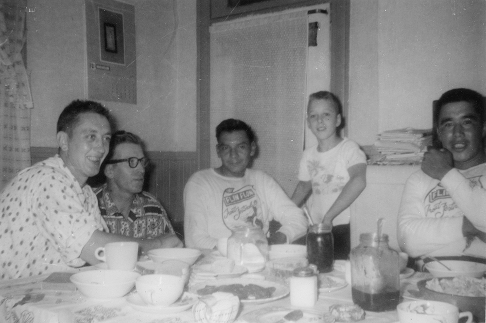Several people are gathered around a table: two white men, two Indigenous men and a young white boy.