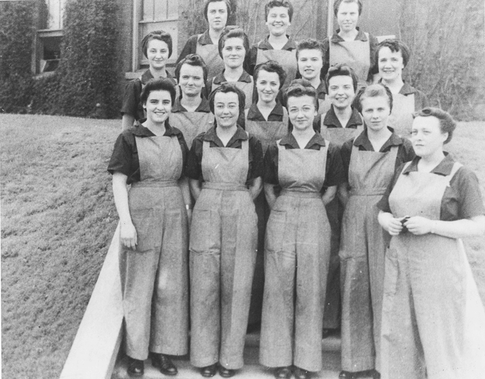 A group of women in work clothes pose in front of a brick building.