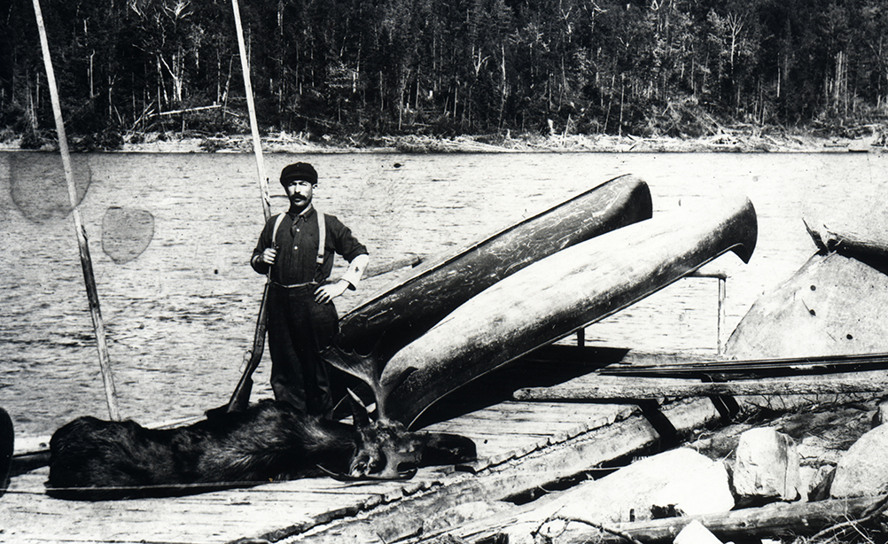 A man poses with a moose carcass on a dock in front of a lake.