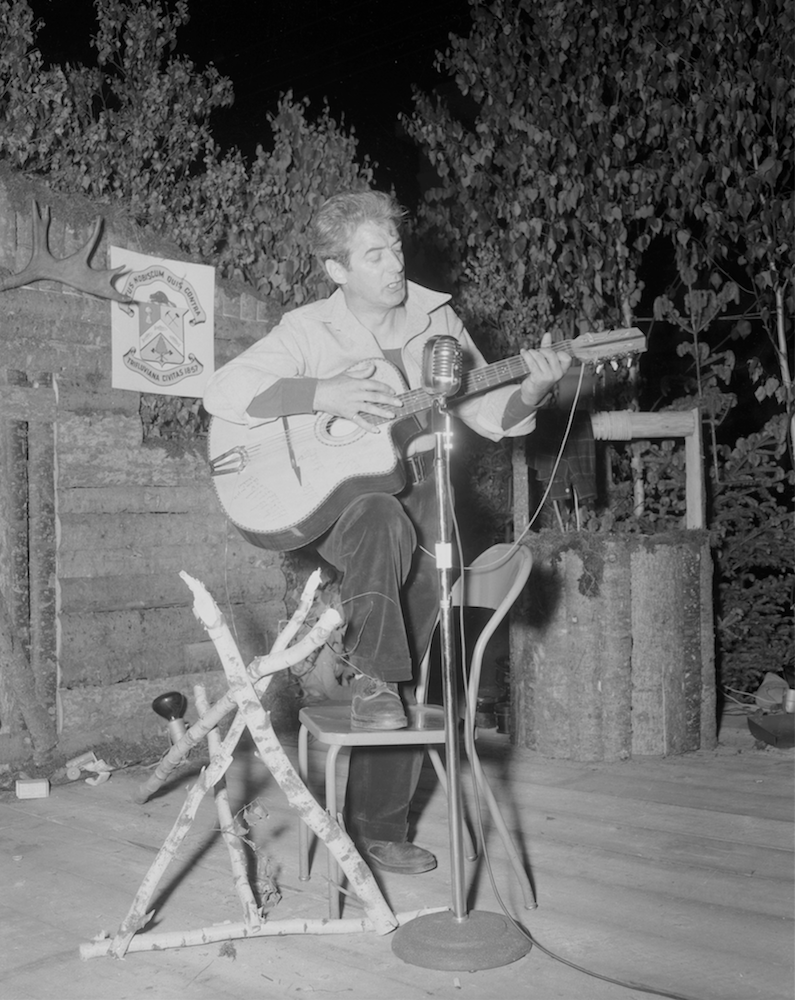Félix Leclerc sings and plays guitar on a stage decorated with logs