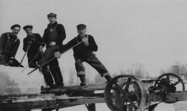Black and white photograph of four ice cutters loading a trailer with huge blocks of ice.