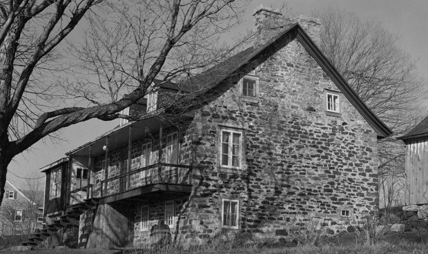 Black and white photograph of an 18th-century stone and wood house, side view. The house has solid stone chimneys and a large wooden porch.