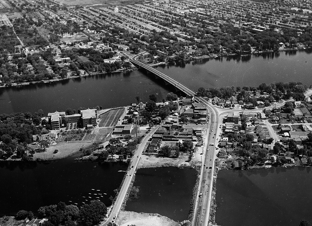 Black and white aerial view of a bridge spanning a wide river. There are neighbourhoods on both shores.