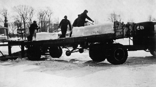 Black and white photograph of a trailer onto which four men are loading huge blocks of ice.