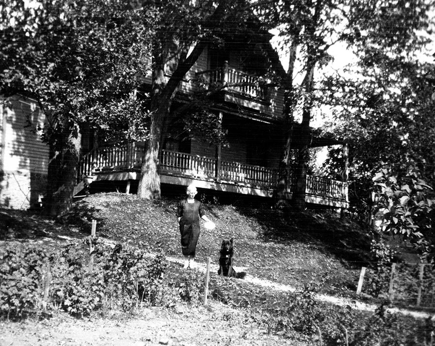Black and white photograph of a woman standing with her dog on a road in front of a large house in summer.