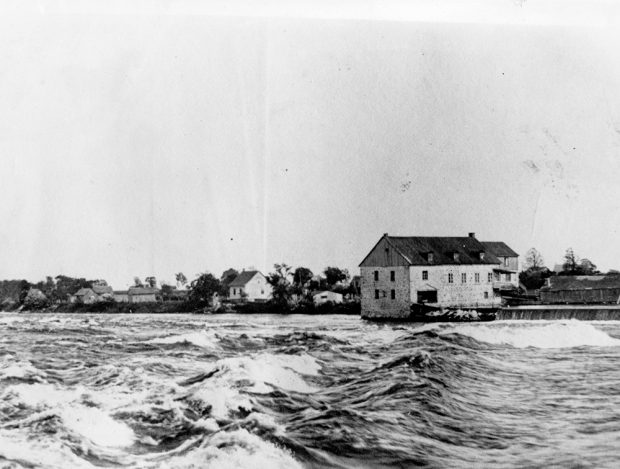 Black and white photograph of a mill in the distance. A river flows in the foreground. The waves are rough.