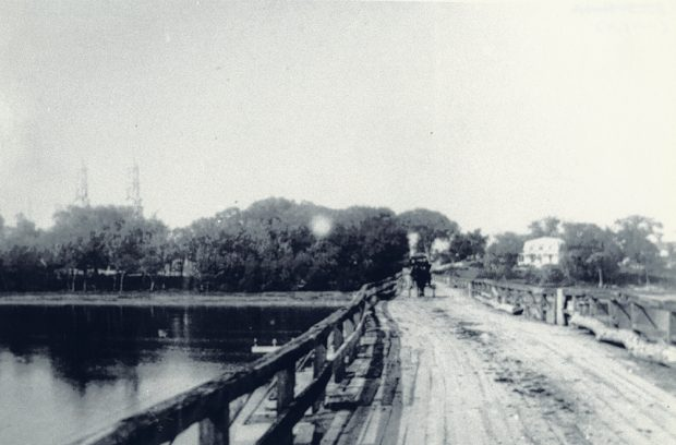 Black and white photograph of the Bellefeuille Bridge. The wooden bridge, with railings on the sides, is not straight. A sled can be seen at the far end.