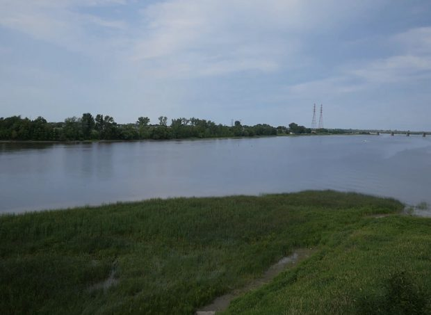 The video begins above the shores of the eastern portion of Île Jésus in summer. The trees and grass are dark green. The camera rises gradually above the trees. The Mille Îles River appears. The camera turns to focus on the area where the two rivers meet. In the distance, you can see the Charles De Gaulle Bridge in Repentigny and the St. Lawrence River. A boat is moving in the water and cars are travelling on the bridge.
