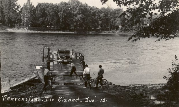 Black and white photograph. A car is parked on the ferry deck. Men on bicycles are waiting their turn. The shoreline of Île Bizard can be seen in the background.
