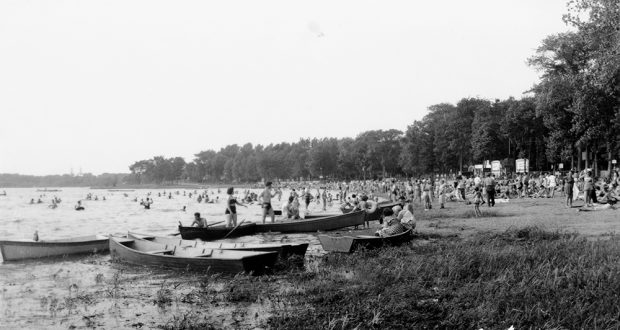 Black and white photograph of a beach with boats and lots of bathers. The beach is surrounded by many trees.