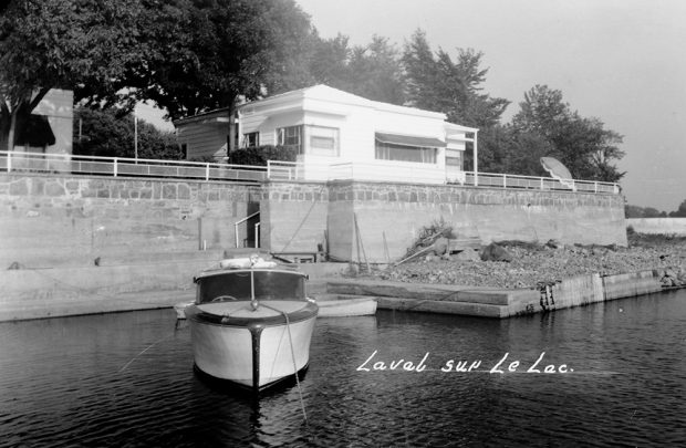 Black and white photograph of a white house with a small pleasure boat tied up at a grey stone dock.