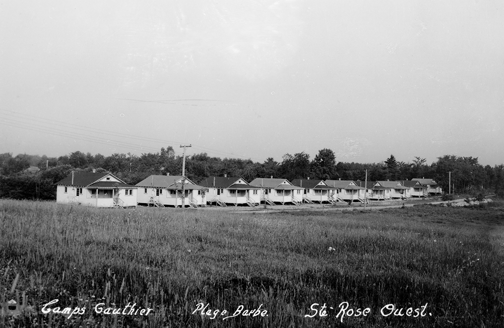 Black and white photograph of a group of small identical white wooden cottages, built side by side.