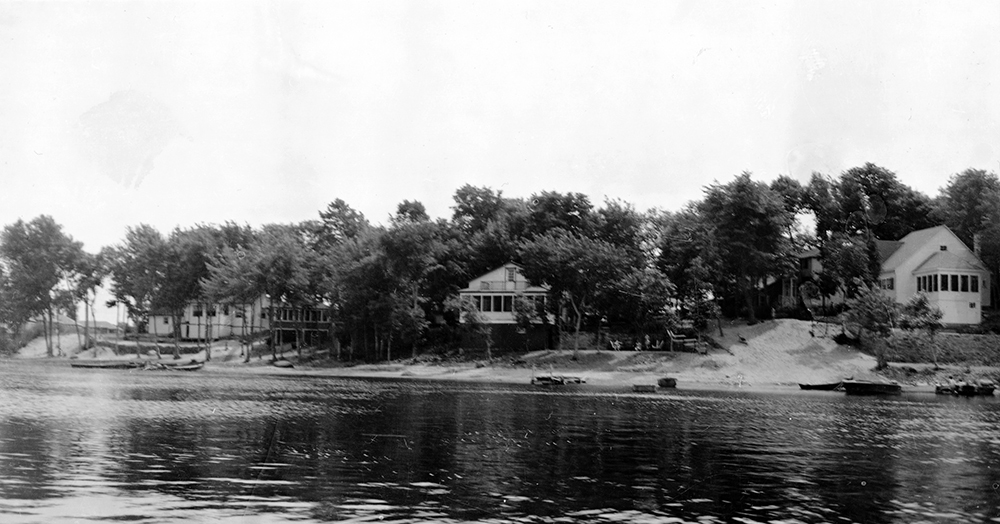 Black and white photograph of three wooden cottages surrounded by trees on a river.