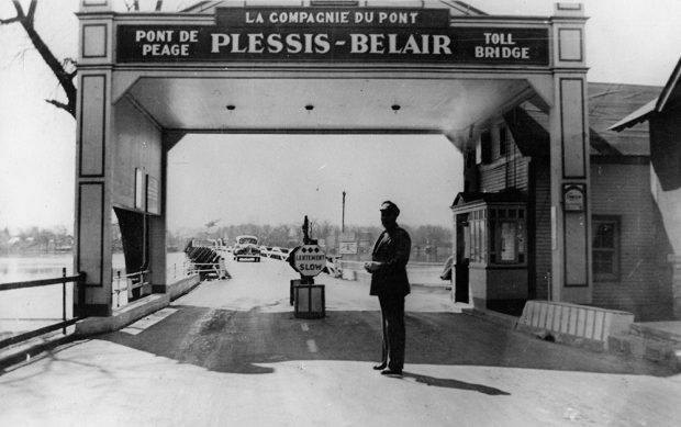 "Black and white photograph of the entrance to the Plessis-Bélair Bridge. The name of the bridge and the words ""pont à péage / toll bridge"" are written on an arch. A security guard stands in front of the toll booth."
