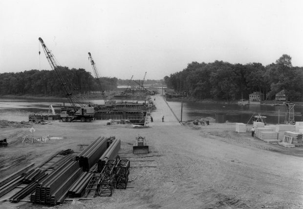 Black and white photograph of Highway 15 being built. Two workers, a crane and construction materials are visible, as well as large metal beams and pieces of wood.