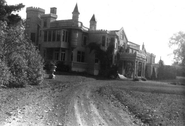 Black and white photograph of a large manor house and a dirt drive. The house has an irregular roofline with turrets and gables.