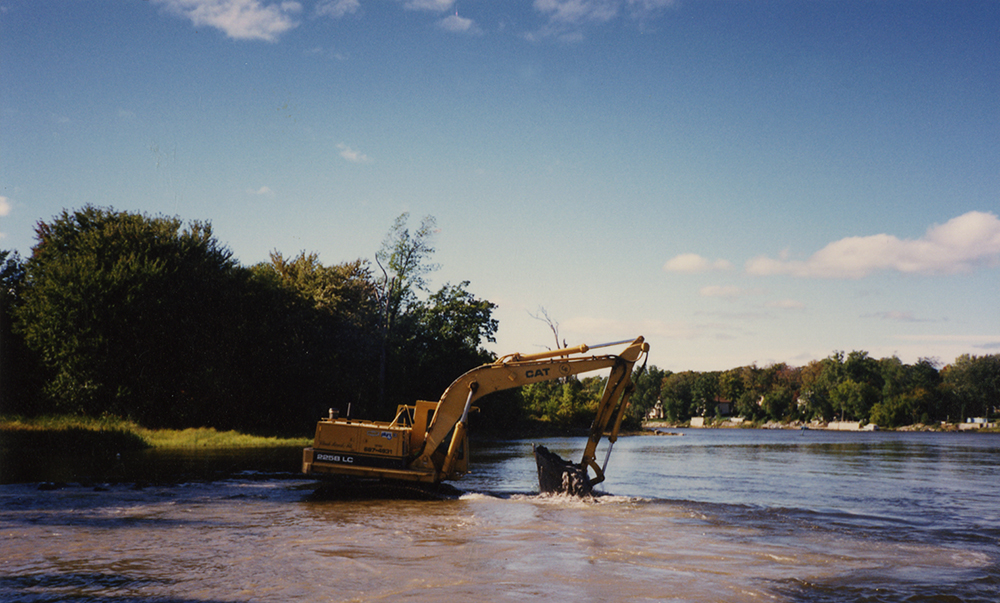 Colour photograph of a yellow mechanical shovel doing clean-up work on the Des Prairies River on a sunny summer day.