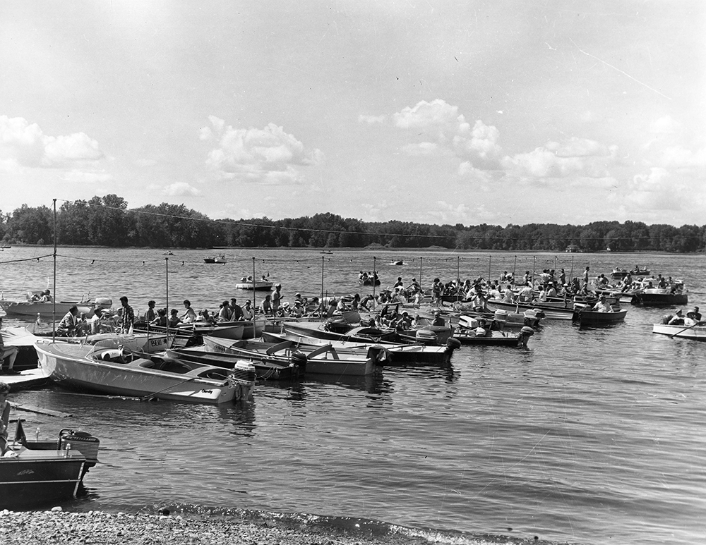 Black and white photograph of small motorboats moored to a dock. Many people are sitting in them, ready for a boat parade.