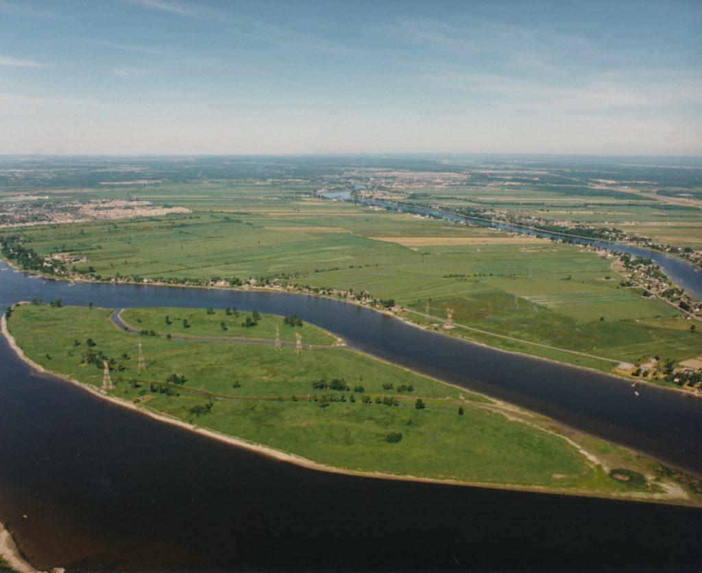 Photographie aérienne en couleur de l'Archipel du Mitan entouré de la rivière des Prairies en été. L'archipel est verdoyant.