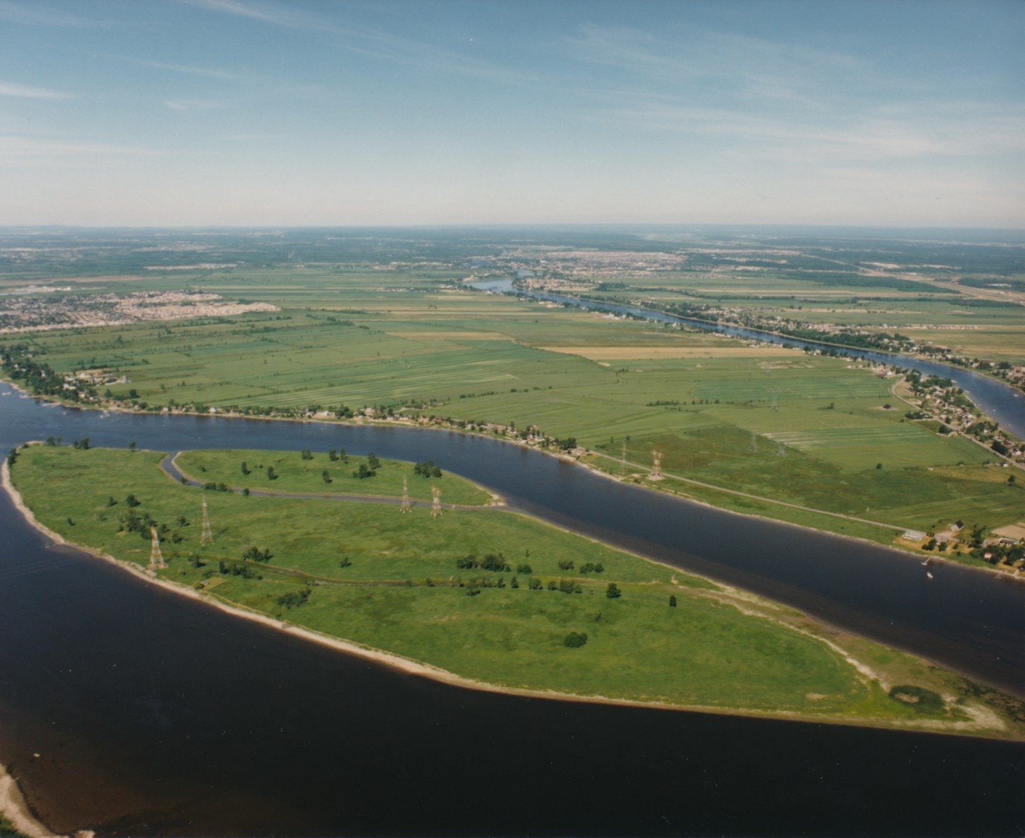 Colour aerial photograph of the Mitan archipelago surrounded by the Des Prairies River in summer. The islands are a lush green.