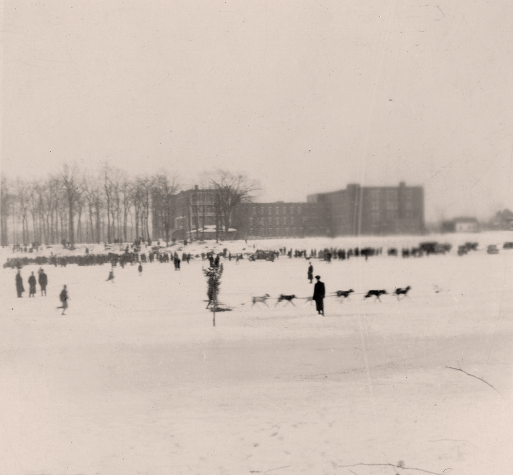 Black and white photograph of a dogsled race on the Des Prairies River in winter. Hundreds of people are standing on the river's snowy shore and six dogs harnessed together are pulling a sled.