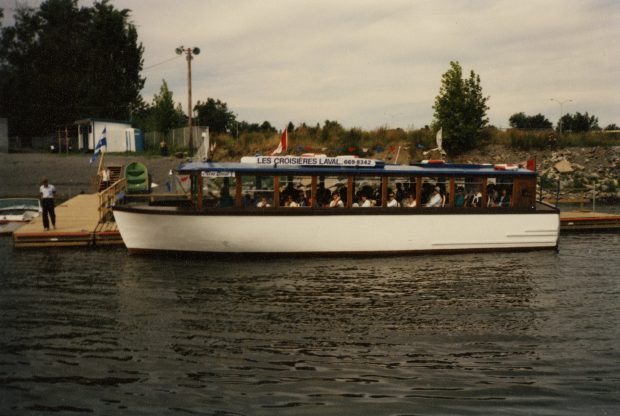 Colour photograph of a white boat moored and filled with passengers ready for a cruise on the Des Prairies River.