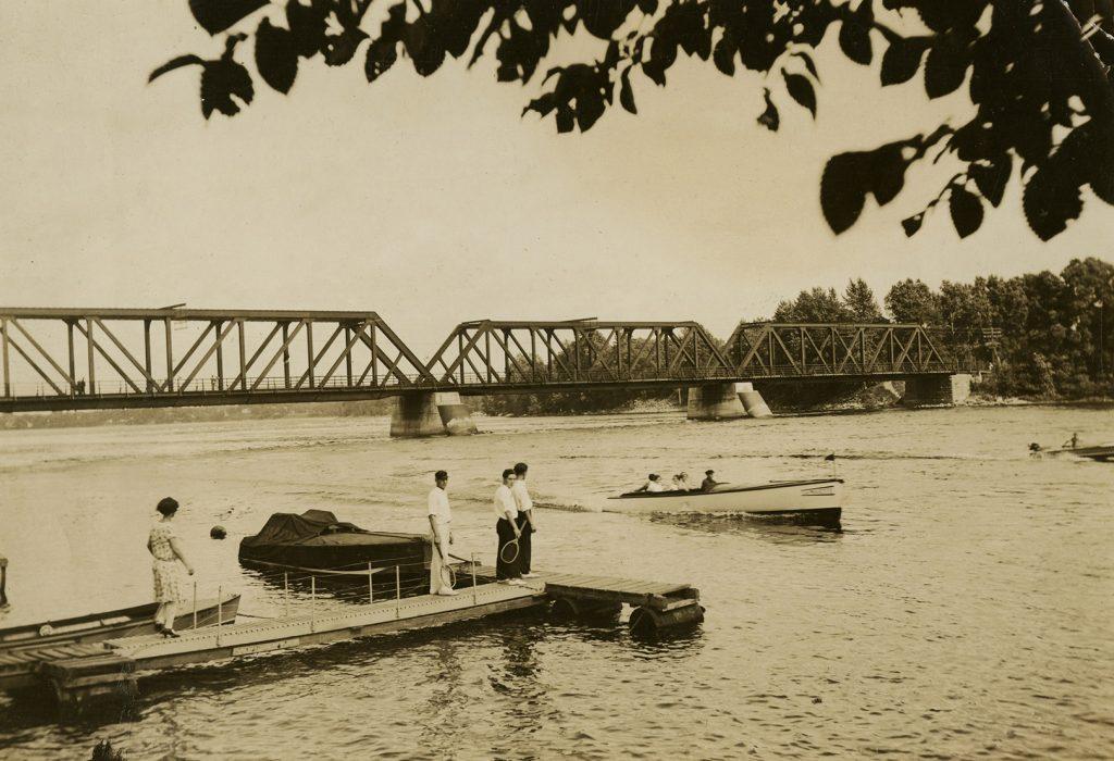 Photographie en sépia de gens sur un quai regardant des embarcations à moteur sur la rivière. En arrière-plan, un pont pour les trains enjambe la rivière.