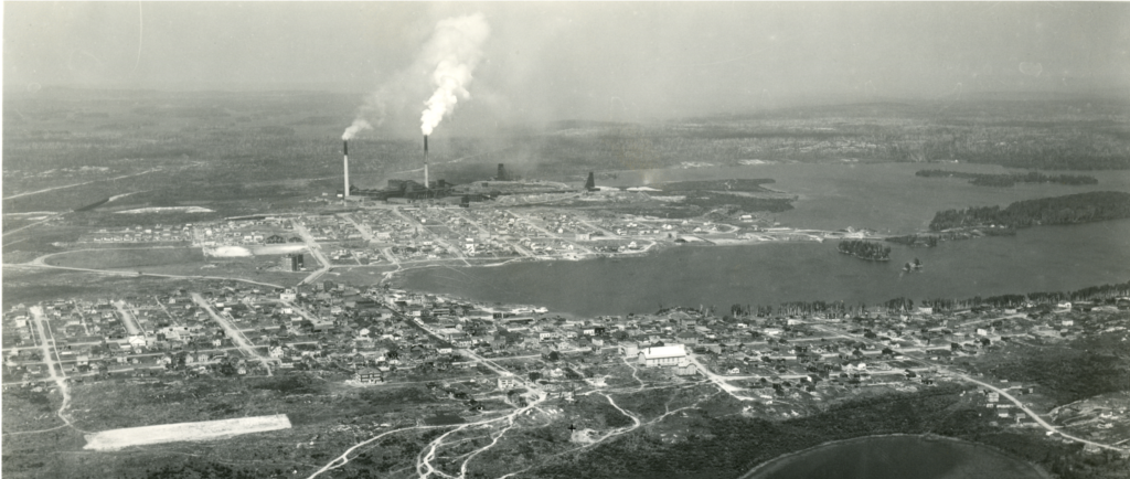 Black-and-white photograph of two cities build around a lake, separated by a vacant lot. In the background, you can see the smelter with three headframes and two smoking chimneys.