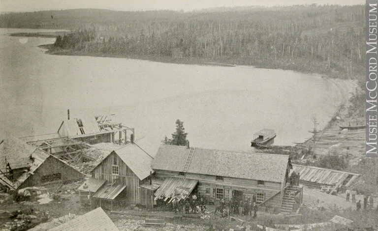 Black-and-white photograph of about fifteen people in front of the four Wright Mine's wood buildings located along the shores of Lake Timiskaming.