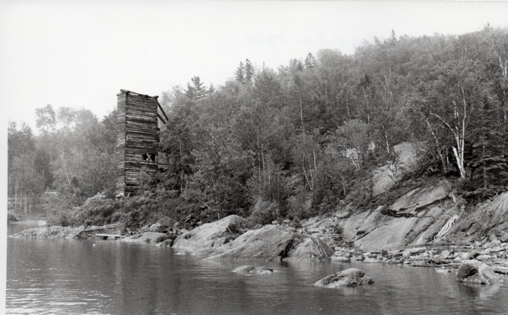 Black-and-white photograph of the shores of Lake Timiskaming, lined with rocks and trees, with a squared high-tower made of wooden planks.