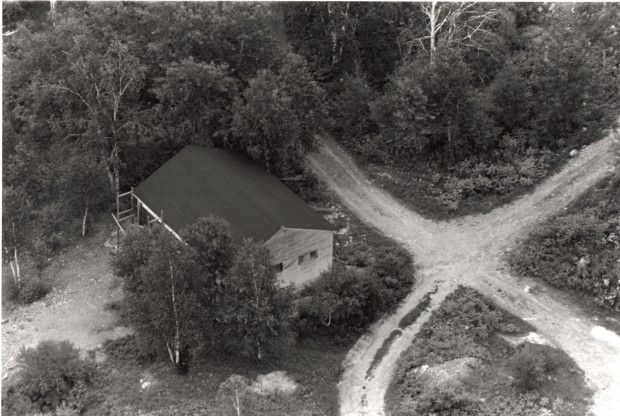 Black-and-white aerial view photograph of a wood building surrounded by trees at the intersection of two gravel paths.