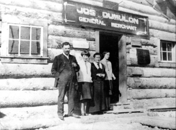 Black-and-white photograph of four people before a log front and a sign that reads, Jos Dumulon General Merchant.