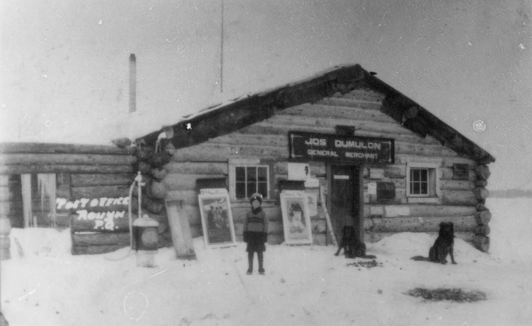 Black-and-white photograph of a log cabin with a sign that reads, Jos Dumulon General Merchant. In front, you can see a young boy with two dogs.