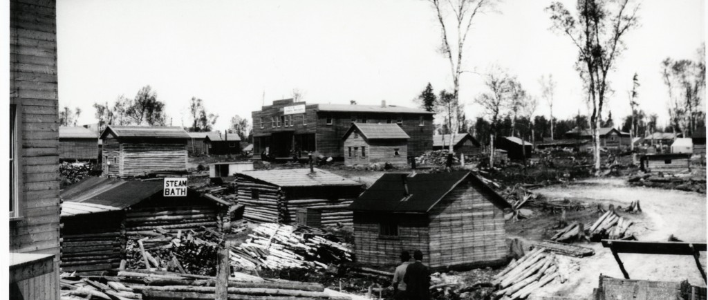 Black-and-white photograph of several rudimentary buildings made of wooden planks or timbers. One of them is a steam bath, identified as such on a sign.