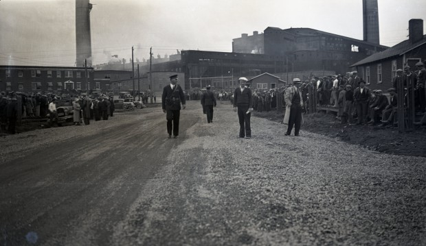 Black-and-white photograph of a road with people on opposite sides and five police officers in the middle, two of whom are wearing uniforms. You can see the smelter in the background.