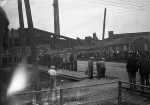 Black-and-white photograph of people gathered on two opposite sidewalks in front of the Horne smelter.