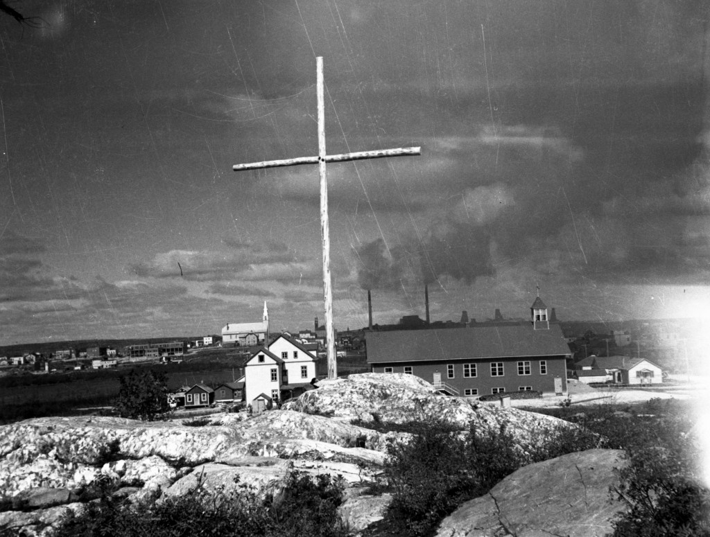Black-and-white photograph of rocks, a cross, a church and a rectory. In the background, you can see Rouyn city on the left and the Horne mine facilities on the right.