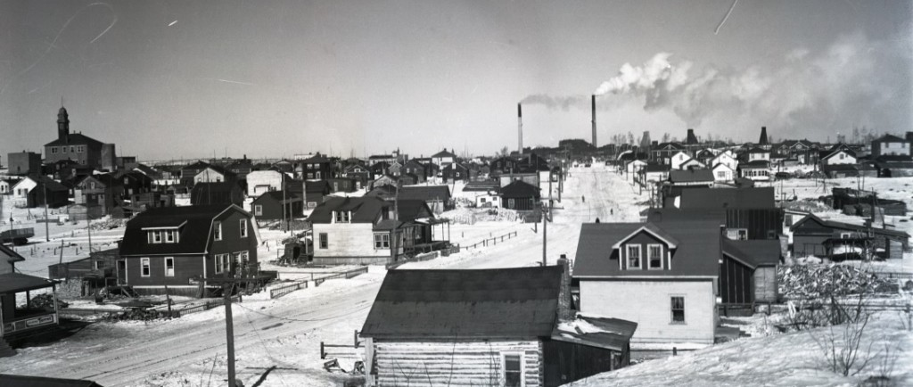 Black-and-white photograph of Galipeau Street now known as Larivière Street. In the background there is the Rouyn City Hall on the left and the Horne mine on the right.