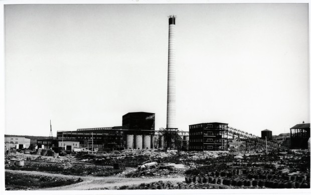 Black-and-white photograph of the construction of the Horne smelter. You can see a chimney in the middle, and many building materials in the foreground.