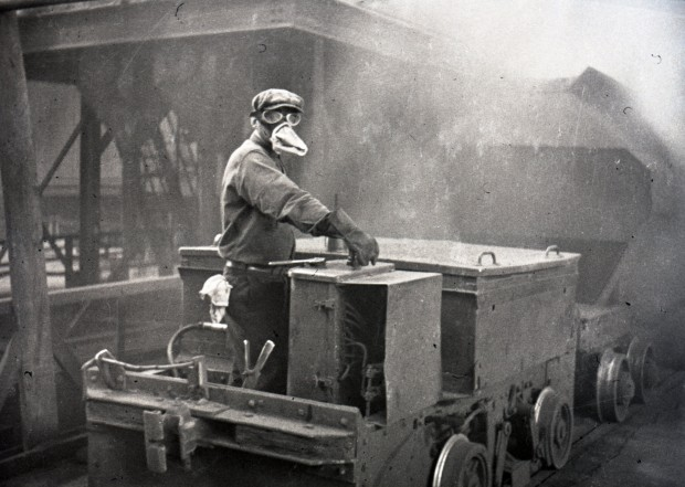 Black-and-white photograph of a worker wearing a protective mask and safety goggles while driving a car inside the Horne mine's smelter. The picture looks blurred because of the gases, but you can see the steel structures.