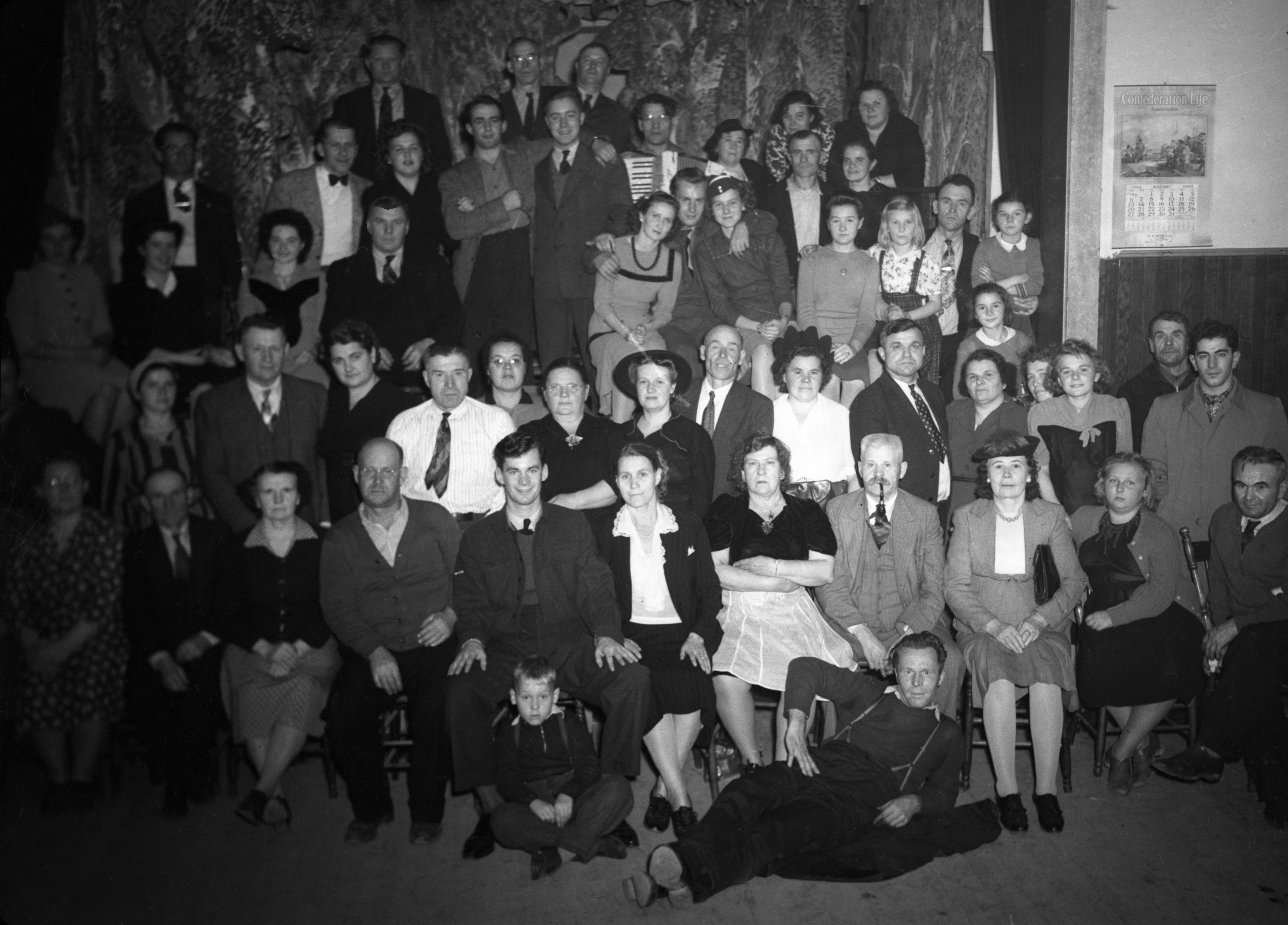 Black-and-white photograph of about 50 people: 23 women, 24 men and a few children. One person is holding an accordion.